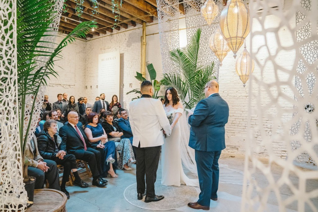 Bride and groom say vows in front of audience in background at the White Room of Regency Event Venue in Red Hook