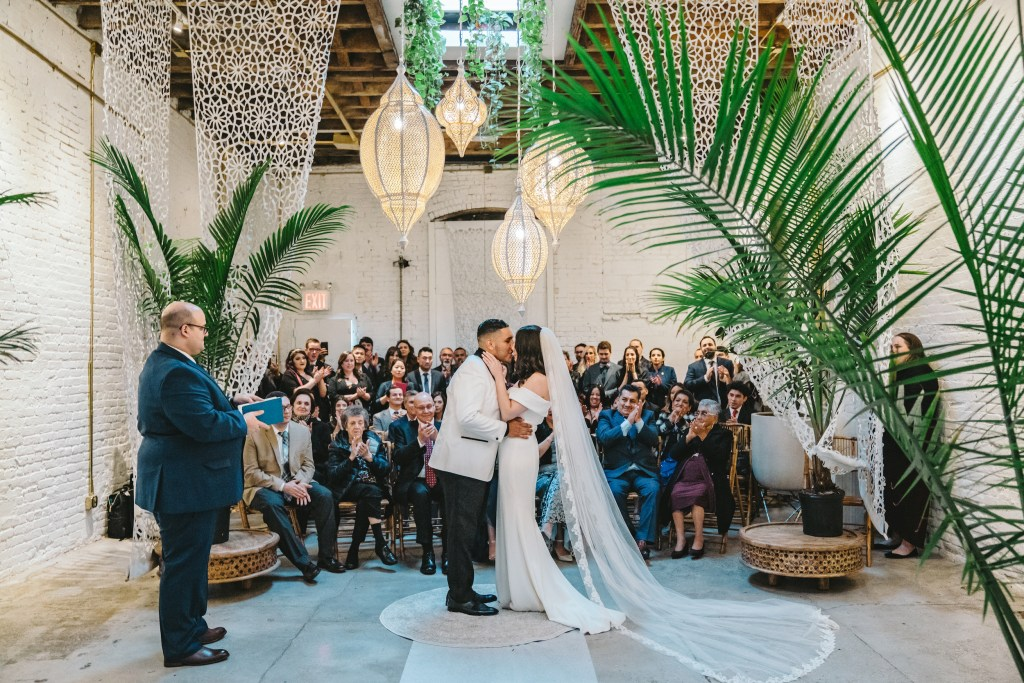 Bride in white wedding dress and groom kiss each other sweetly at Regency Event Venue
