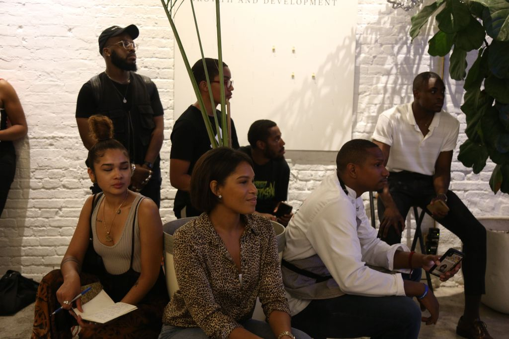 People sit listening to speaker at a workshop by Project 96 summer activation experience