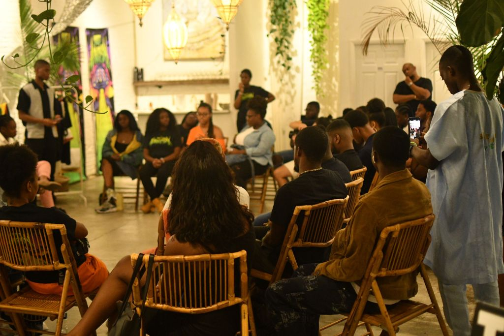 People sit in chairs having discussion at a workshop by Project 96 summer activation experience