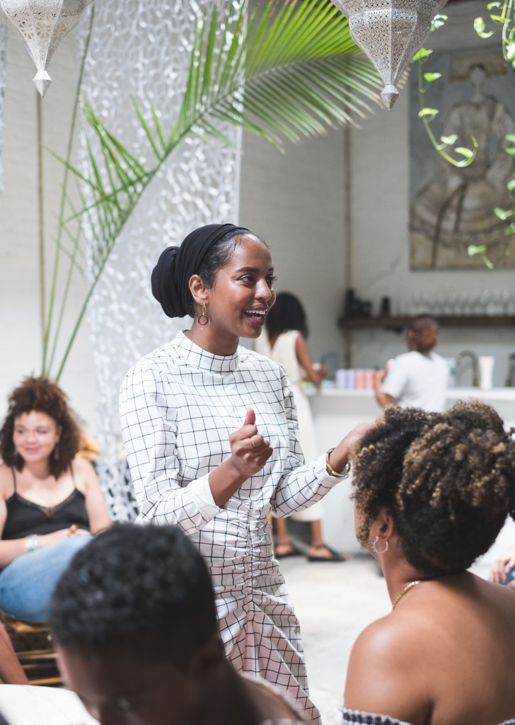 Women in white speaks passionately at the White Room of Regency Community and Event Space