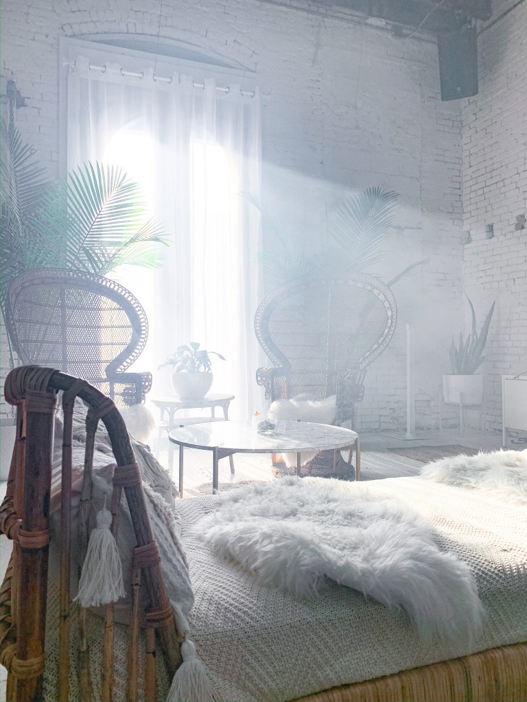 Bed with fur with high-backed chairs and plants in the background in Regency event venue
