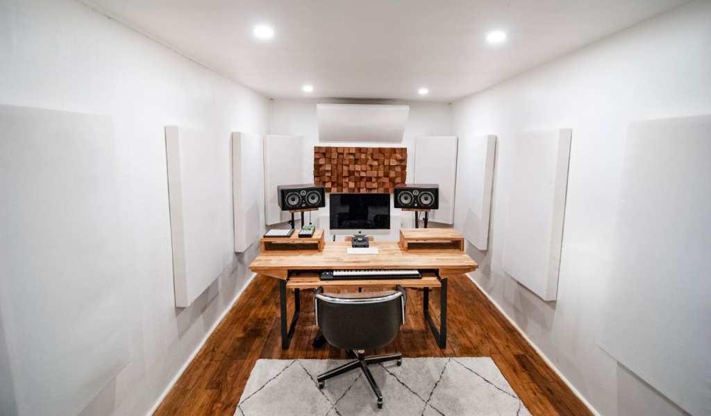 All-White room with acoustic paneling, instruments on the wall at the Regency Recording studio