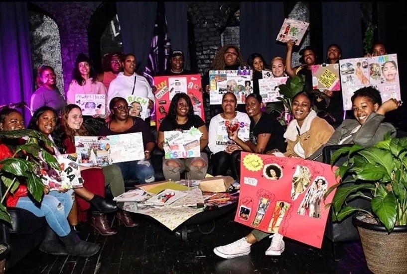 People holds up poster boards for an event in the black room