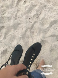 walking on the beach shoes in hand