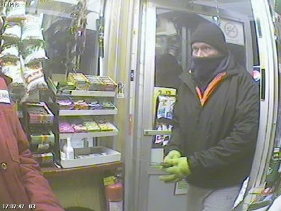 The suspect is described as male, approximately six feet tall, around 200 lbs., late 30's – 40's, red hair, blue-green eyes, wearing grey pants, a blue jacket over an orange hoodie over a second blue hoodie beneath, a black toque, green gloves, and a dark blue neck warmer which he had pulled over his face just above his nose.