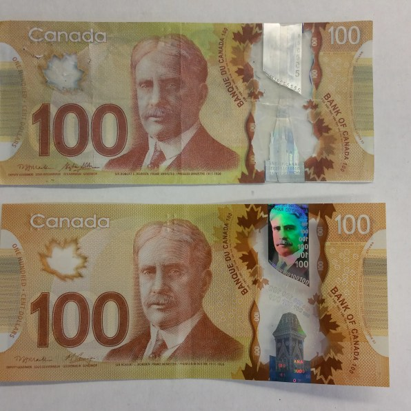 Note that the fake bill (top) has lost a lot of reflective vibrancy in the transparent stripe and maple leaf window. The transparent area of the middle window is from an actual five dollar bill, but the plastic film above it has lessened it's reflective qualities. In a real bill (below) the numbers in the windows match the value of the currency note..