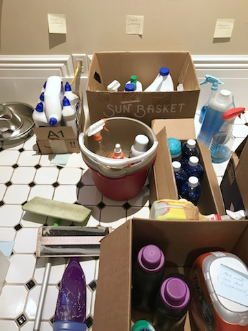 On bathroom floor, boxes and buckets filled with cleaning-related products, mostly liquids.