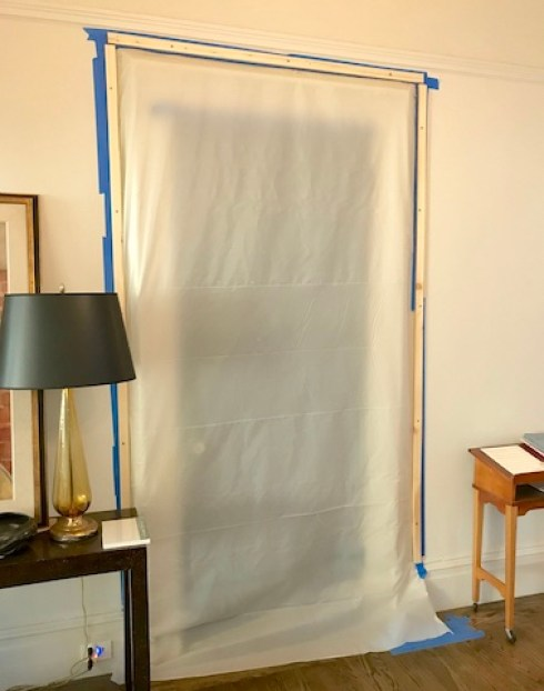 Plastic sheet taped over doorway. To left is lamp on table. To right is music notes on another table.