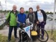 4 Teilnehmer der Velo-Tour mit Wimpel geschmückten Fahrrädern vor der Kulisse des Weiler Yachthafen