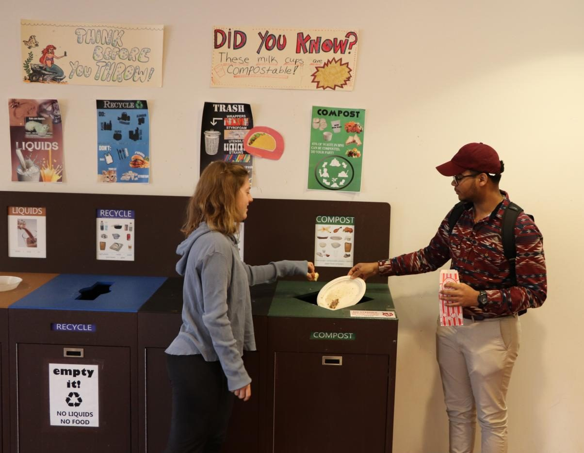 Pictured: Students using the compost bin in the Media Caf.