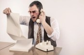 Blockchain: Angry man yelling on phone while reading vintage printer paper report. Photo by SHutterstock