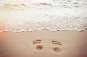 Sand footprints photo via Shutterstock