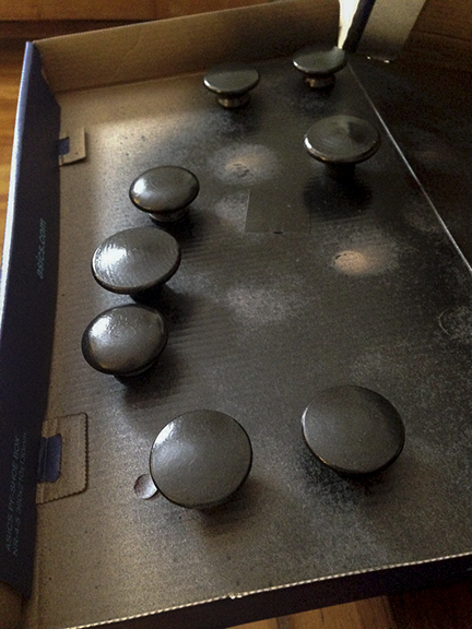Oil-rubbed bronze spray paint on wooden cabinet knobs.