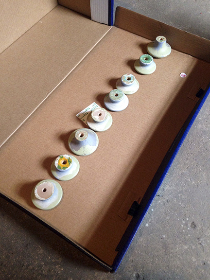Old wooden knobs placed in a row to be spray painted.
