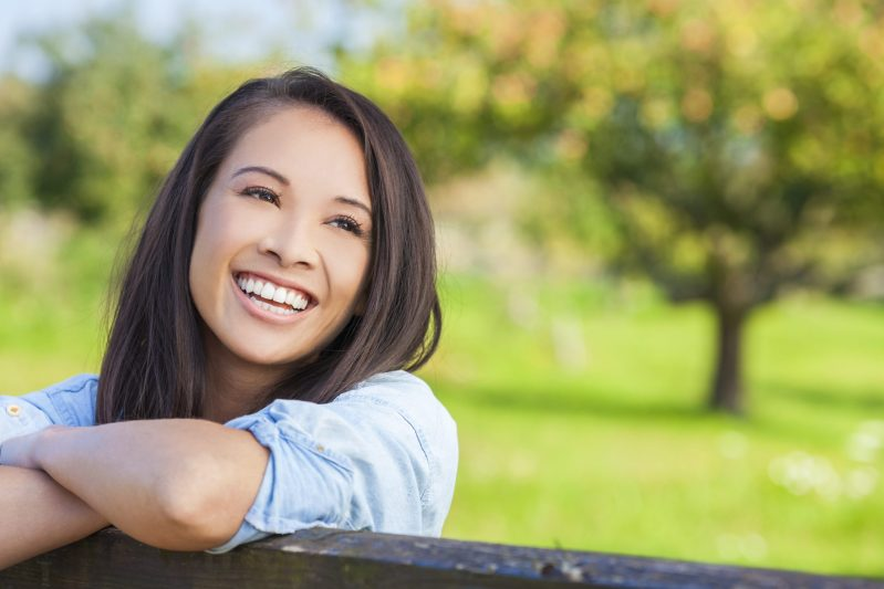 Denatl Care Plan Reogate Dental Centre Cheerful mature woman enjoying in park during sunset near reigate dental centre Happy hispanic woman in casual feeling relaxed outdoor. Smiling brunette woman looking at camera with carefree.