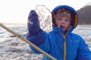 Kleinkind hält Eisbrocken in die Höhe