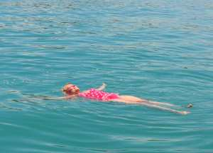 Frau im roten Badeanzug schwimmt im warmen Meer