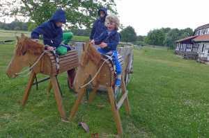 Drei Kinder auf Holzpferden im großen Garten vom Stolperhof, Familienurlaub Usedom, Tipps Familienreise, Aktivurlaub mit der Familie, Usedom-Urlaub, Reiseblog. Reisefeder