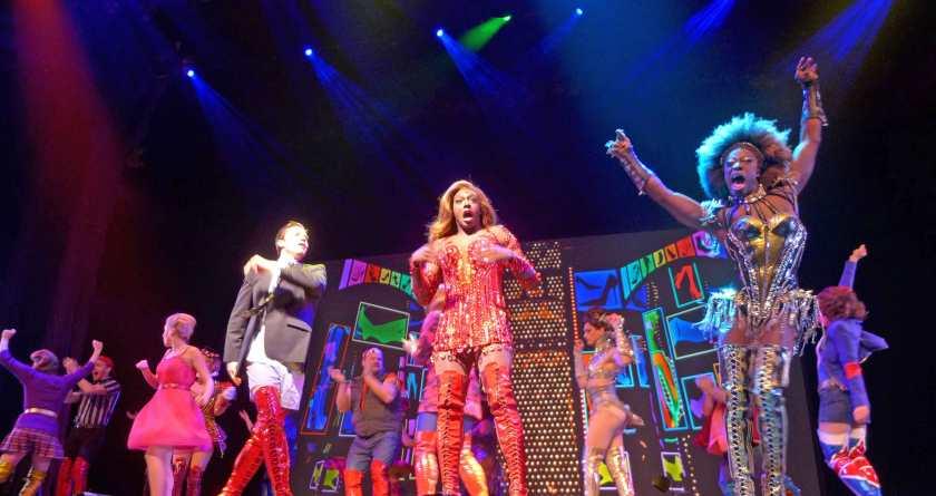 Schauspieler im Musical Kinky Boots tragen rote Schnürstiefel, die bis übers Knie reichen.