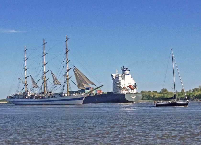 Dreimaster Mir, ein russisches Segelschulschiff, passiert einen Containerfrachter auf der Elbe