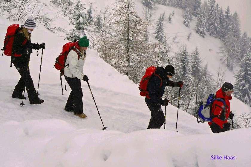 Winterwanderer mit Stöcken im Schnee