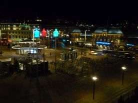 Vor dem Hauptbahnhof sitzen leuchtende Gestalten