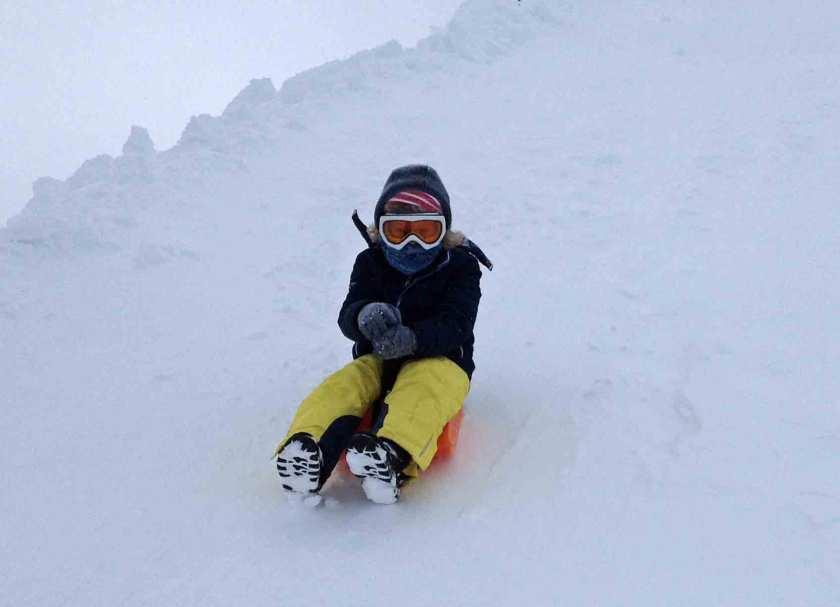 Dick eingemummeltes Kind auf einem Schlitten auf der Zugspitze im Nebel und SDchnee