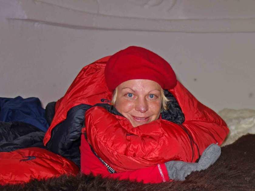 Silke kuschelt im roten Daunenschlafsack im Iglu