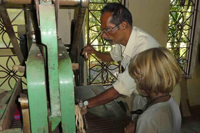 Mann und Kind betätigen eine Buchschneidemaschine
