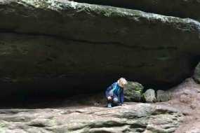 Kind klettert unter einem großen Felsenin der Sächischen Schweiz