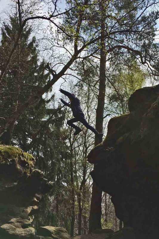 Kind springt über eine Schlucht im Elbsandsteingebirge