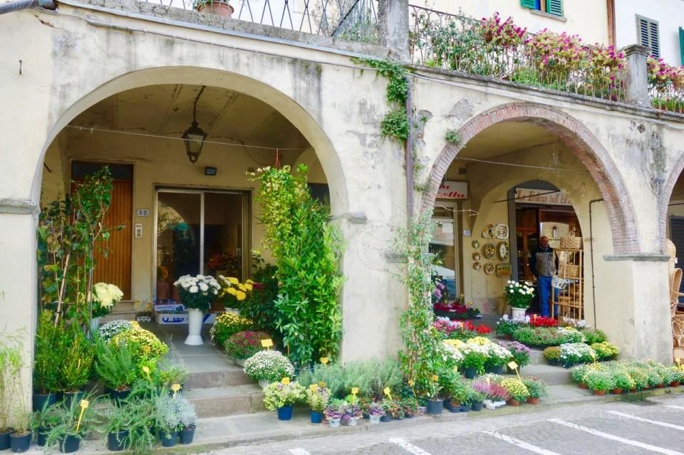Blomster under arkader på torget i Greve in Chianti