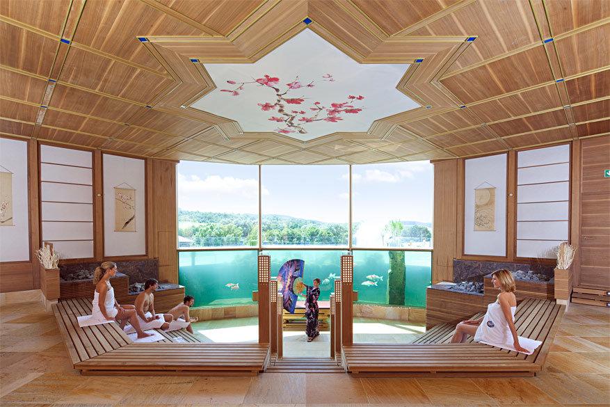 De grootste sauna ter wereld kijkt op uit een aquarium vol koi vissen!