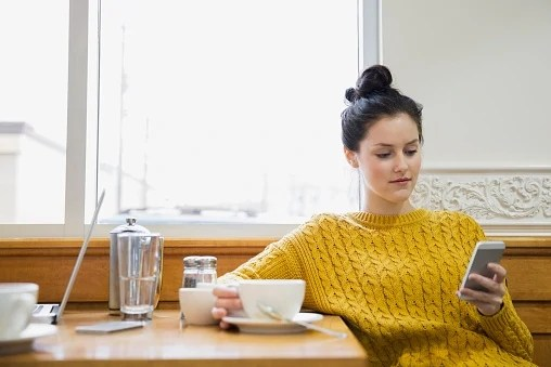 Woman texting and drinking cappuccino in cafe