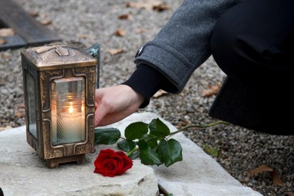 Mature woman lighting candle in lantern at grave in cemetery