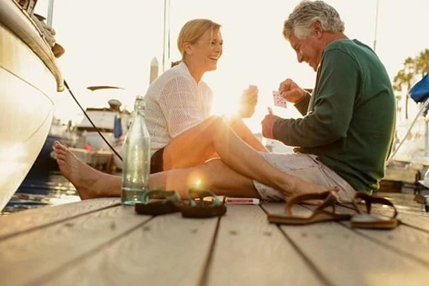 Couple sitting on marina pier playing cards, Redondo Beach, California, USA