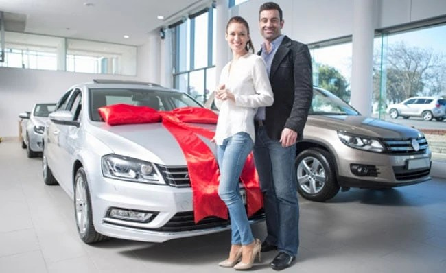 Portrait of mid adult couple and new car with red bow in car dealership