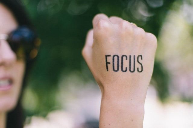 pic of a woman's right fiest saying be focused
