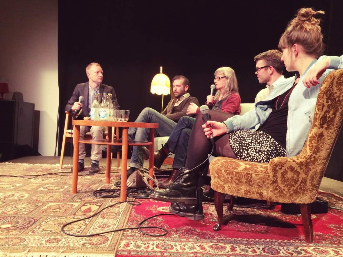 Fem personer på en scen med mikrofoner sittandes i soffor