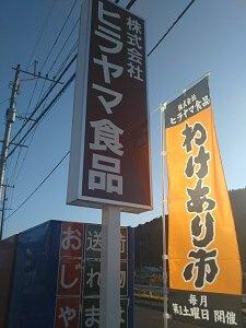会社名の立て看板の横にわけあり市ののれんがある写真