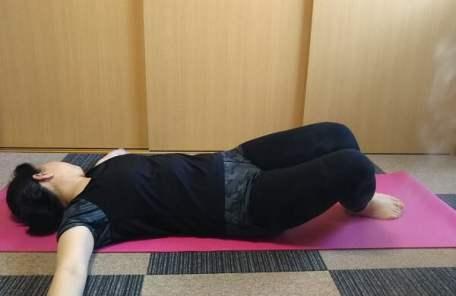 両手を開き、立てた膝と反対側に頭を傾けるストレッチの写真
