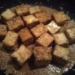フライパンを熱して厚揚げ、調味料、ごまを入れた写真