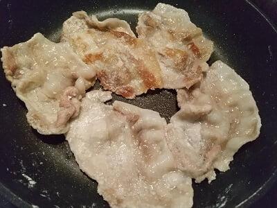 豚肉に片栗粉をまぶしフライパンで焼く写真