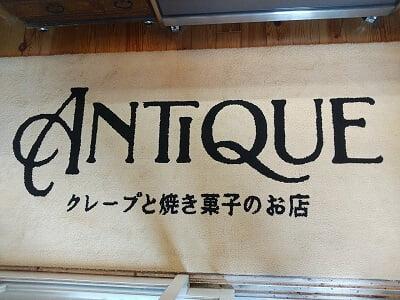 アンティークの足元に店名のマットがある写真