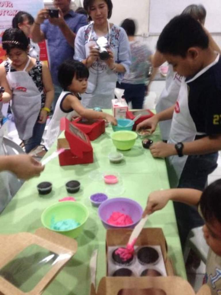 Children making cupcakes and designing them