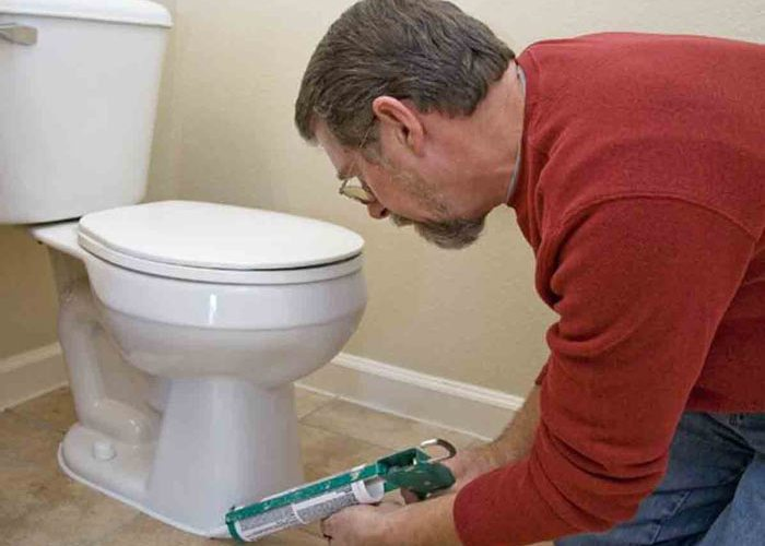 caulking a newly installed toilet with tips from Relief Home Plumbing in Loveland, CO.