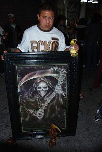 En ung mann med en skremmende avbildning av La Santa Muerte, og en flaske mescalin. Foto: Thelmadatter - Wikimedia Commons.