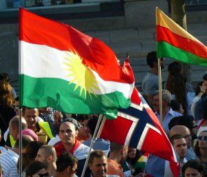 To ulike kurdiske flagg, og ett norsk, ved en kurdisk demonstrasjon på Jernbanetorget i Oslo. Foto: Hans Olav Arnesen.