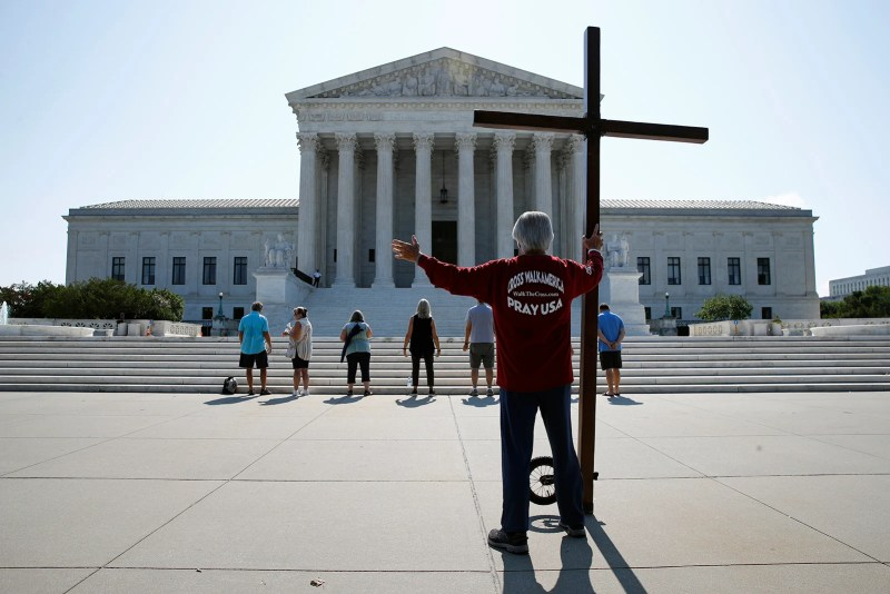 Tom Alexander holds a cross as he prays prior to rulings outside the Supreme Court on Capitol Hill in Washington on July 8, 2020. (AP Photo/Patrick Semansky)